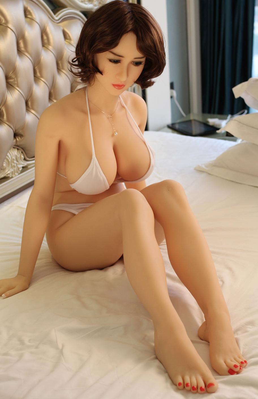 Asiatische Realdoll auf dem Bett sitzend mit Unterwäsche an